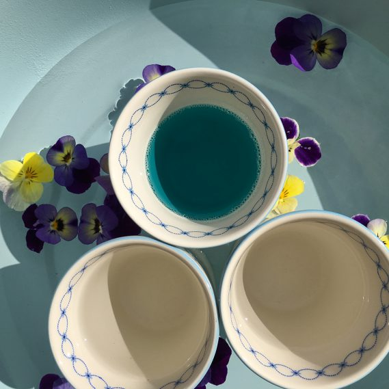 Fußbad, 3 Tassen mit Fussbadzutaten in blauer Wanne mit Hornveilchen, Draufsicht Fußbad