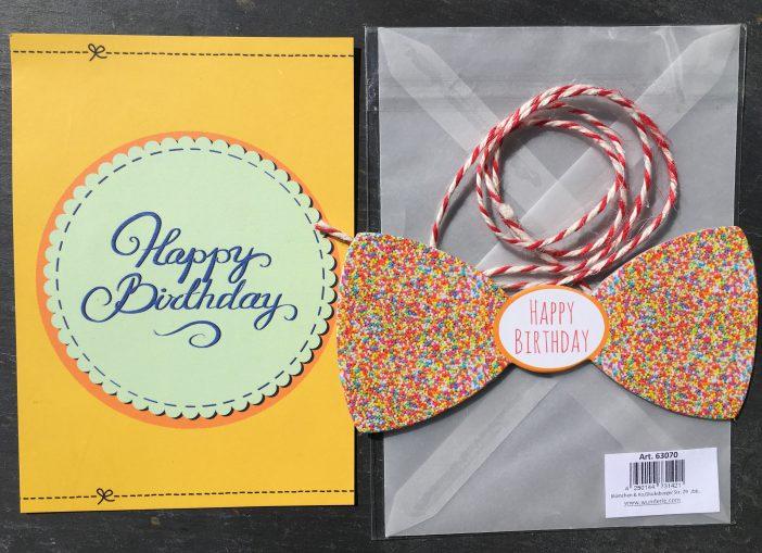 Postkarte, Fliege und Umschlag auf Schiefer