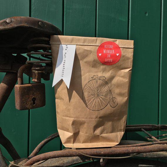 Tüte für Radverrückte auf rostigem Gepäckträger an Sattel gelehnt