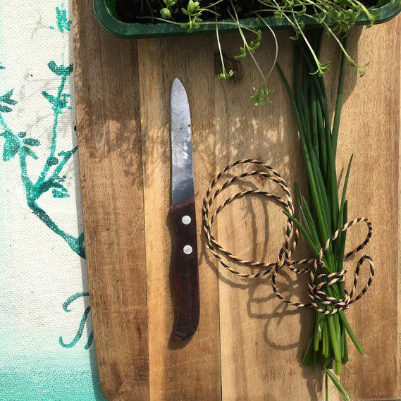 Holzbrett mit Schnittlauchsrauß und Messer