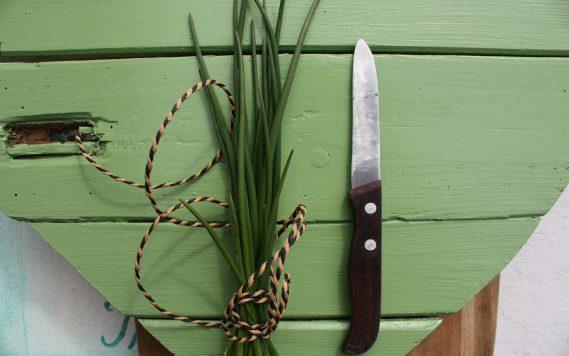 Messer und Schnittlauch auf grünem Holzherz