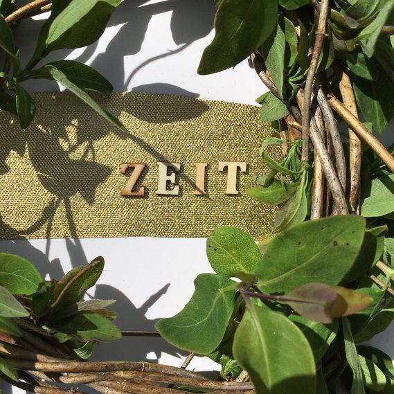 Schriftzug ZEIT aus kleinen Holzbuchstaben auf Gold