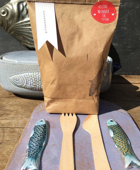 Sterneköchetüte auf blauem Porzellanbrett mit Holzbesteck und Schokoladenfischen Hochformat