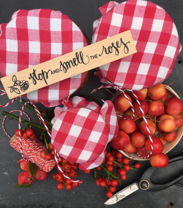 Rot-weiße Marmeladengläser mit Zieräpfeln und roten Accessoires