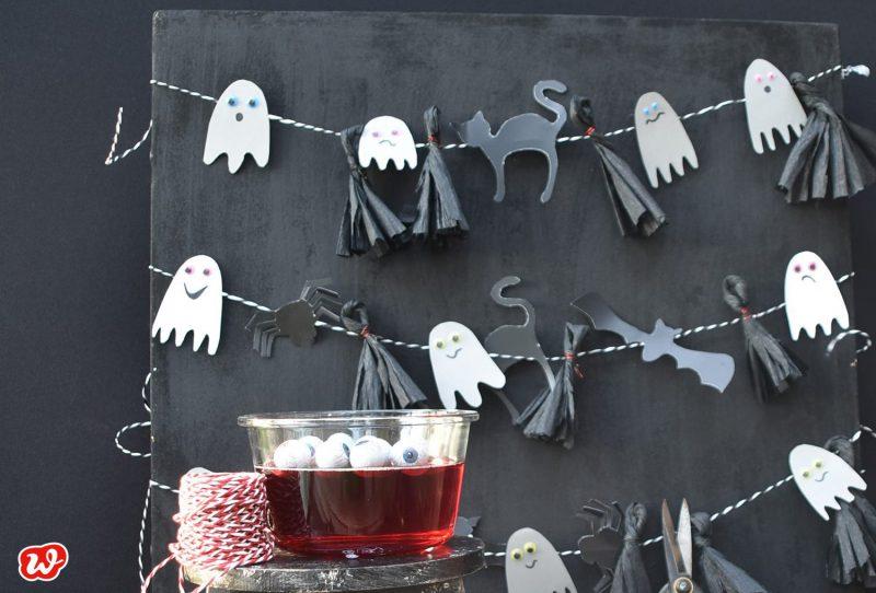Halloweendeko, schwarze Platte mit Gespenstergirlanden, roter Wackelpudding mit Augen im Vordergrund