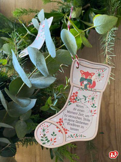 Papierstiefel vom Wunderle Sternadventskalender an Eukalyptuszweig hängend