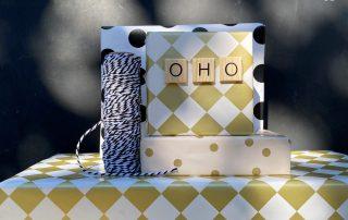 Kleiner geschenkstapel mit Holzbuchstaben Oho