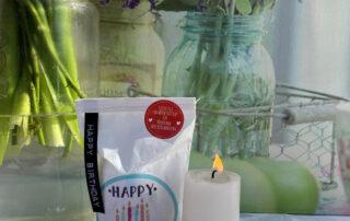 Kleine, weiße Happy Birthday Wundertüte mit brennender Kerze